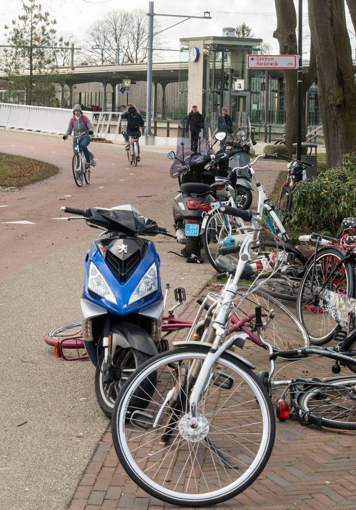 Scooters en fietsen gestald rondom station Harderwijk.