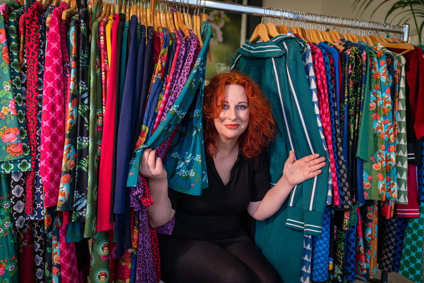 Alisa Sprikkelman tussen de door haar ontworpen jurken van Tante Betsy in het bedrijfspand in Elst.