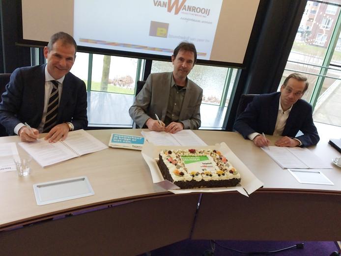 Projectontwikkelaar Clemie van Wanrooij (l) en directeur Jan van Peer (r) van het gelijknamige bouwbedrijf, ondertekenen samen met wethouder Peter van de Wiel de overeenkomst voor 465 woningen in Boxtel-Noord.