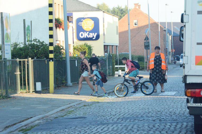 Een gemachtigd toezichter helpt de scholieren over aan basisschool De Wegwijzer. De leerlingen komen zelden per fiets omdat het wegdek er slecht ligt.