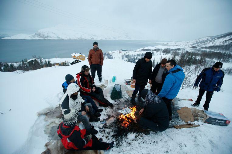 Asielzoekers zijn aan het koken bij een kamp in Seiland, een eiland in het noorden van Noorwegen. Beeld AP