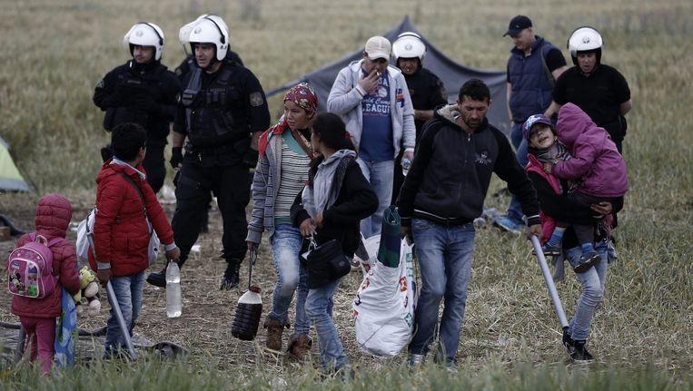 Een gezin loopt mee met Griekse oproerpolitie. Beeld null