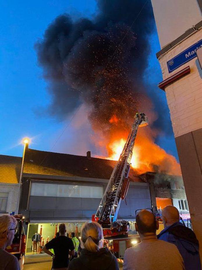 De hoge vlammen sloegen uit het pand. Buurtbewoners komen kijken naar de vlammenzee.
