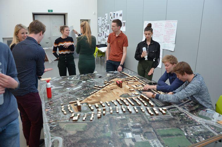 De studenten gaan in gesprek over de toekomst van Nieuw Gent bij een maquette van de wijk.