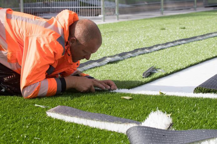 Kunstgras wordt aangelegd op een sportveld.