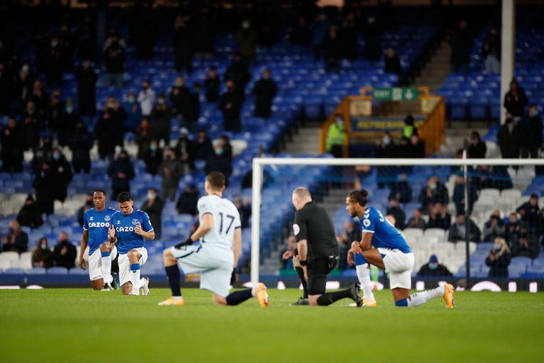 Spelers van Everton en Chelsea knielen voor de wedstrijd. Beeld EPA