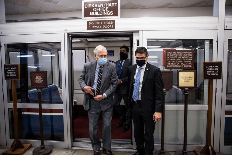 De Republikeinse leider in de Senaat, Mitch McConnell (links op de foto) dinsdag onderweg naar het Capitool in Washington, waar hij ondanks zijn aanvankelijke veroordeling van Trumps 'leugens', toch tegen diens impeachment zal stemmen. Beeld Getty Images