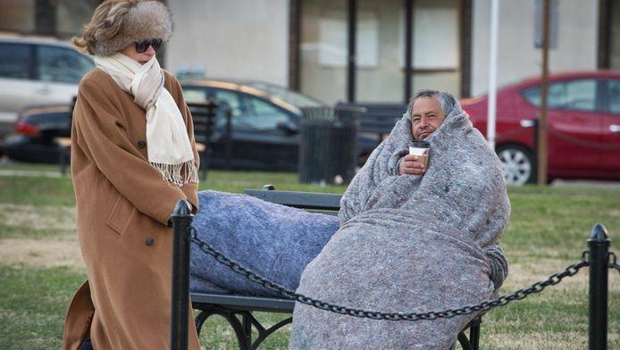 Een vrouw passeert een dakloze man die de winterse kou van Washington trotseert
