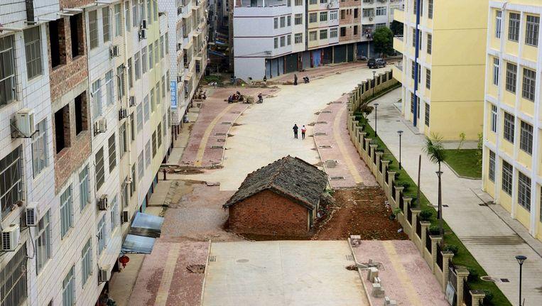 Een huis waarvan de eigenaar het weigerde te verkopen, middenin een weg in aanleg in Nanning, China. Beeld reuters
