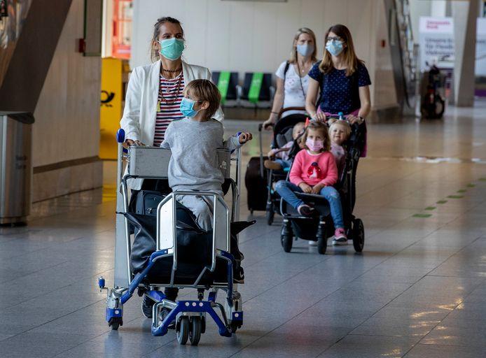 Partners en kinderen van de in China werkzame Duitsers in de vertrekhal van de luchthaven van Frankfurt.