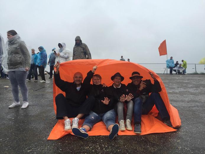 Collega's George en André en hun Jolanda's uit Rotterdam schuilen onder landbouwplastic tijdens het optreden van Typhoon.