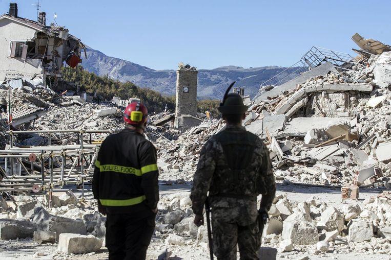 Een brandweerman en een soldaat kijken uit over de vernieling in Amatrice, een stad die opnieuw getroffen werd.  Beeld AP