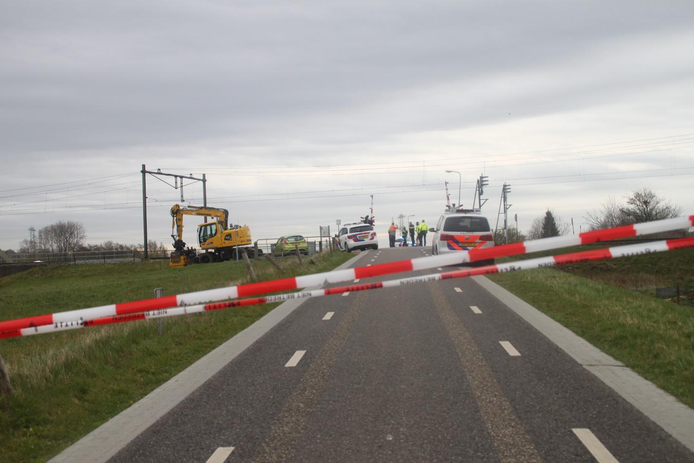 Politiemensen en medewerkers van spoorwegbeheerder ProRail zetten het gebied af rond de vindplaats van een lichaam.