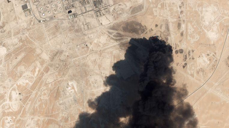 Op een satellietfoto is te zien hoe de grootste olieraffinaderij ter wereld, in Abqaiq in Saudi-Arabië, in brand staat na een aanval. Beeld AFP