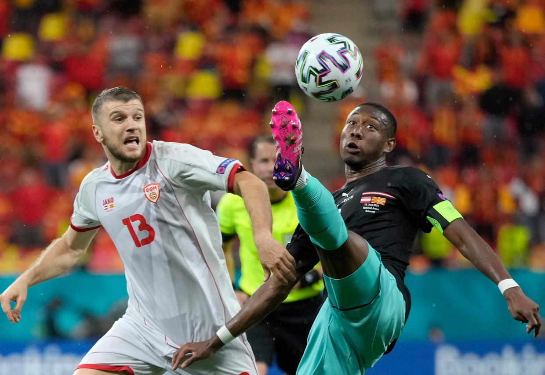 David Alaba trapt de bal acrobatisch weg voor de neus van de Noord-Macedoniër Stefan Ristovski in de eerste groepsmatch. Beeld AP