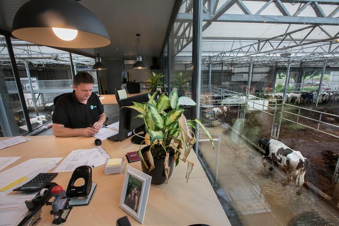Melkveehouder Arjan Geenen kijkt vanuit zijn kantoor uit over zijn nieuwe vrijloopstal.