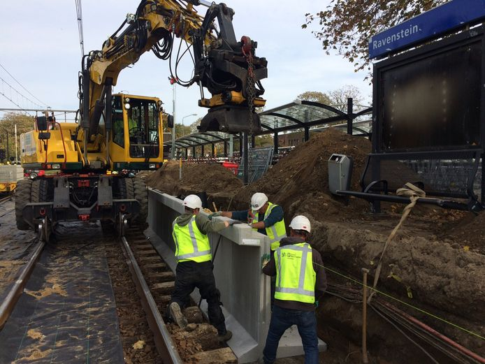 Met een kraan worden de nieuwe keerwanden geplaatst op het station in Ravenstein.