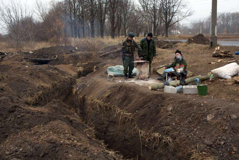 Pro-Russische rebellen naast hun loopgraven in Donetsk. Nadat de NAVO Rusland had beschuldigd meldt Oekraïne dat er in de afgelopen vierentwintig uur vier Oekraïense soldaten zijn gesneuveld en wel achttien gewond zijn geraakt. Beeld afp