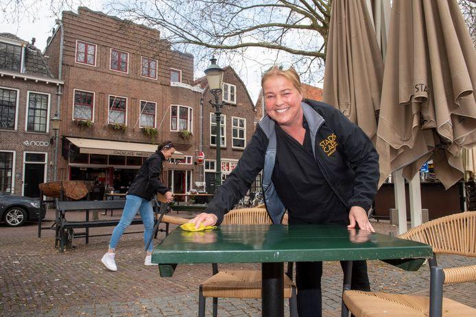 Pauline van Heugten (voorgrond) en Maaike Gouw zetten het terras van het Stadscafé aan het Lieve Vrouwekerkhof uit.