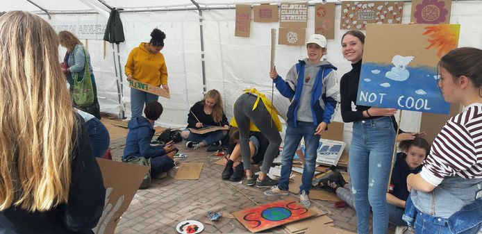 Klimaatdemonstranten maken bij de Walburgiskerk in Arnhem spandoeken en borden met leuzen voorafgaand aan de klimaatmars door de stad.