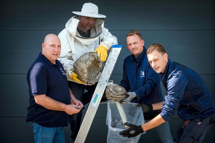 Karel Hofmans (links), zijn beide zonen Zeno (rechts) en Brando (in imkerspak) en medewerker Micha Steenhuis van ongediertebestrijdingsbedrijf DE4 Nederland uit Mijdrecht laten het dak van een wespennest zien, waarin de raten met larven en wespen zitten.