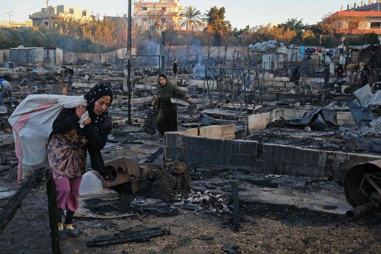 Syrische vluchtelingen in de Libanese provincie Minja zoeken naar hun eigendommen in de smeulende resten van het kamp dat in brand werd gestoken. Beeld AFP