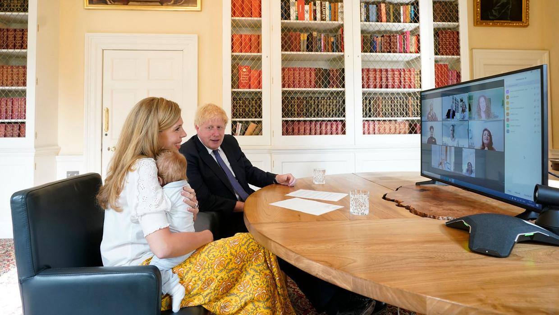 Boris Johnson en verloofde Carrie Symonds met hun baby tijdens een Zoom-meeting. Deze foto leidde tot een heleboel complottheorieën. Beeld rv