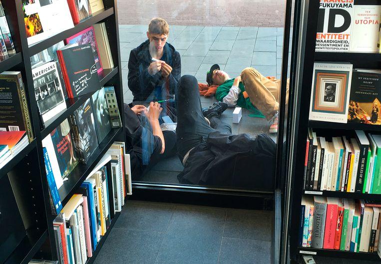 Een groepje jongeren rookt cannabis tegen de gevel van het Van Gogh Museum. Beeld  Paul van Riel/HH