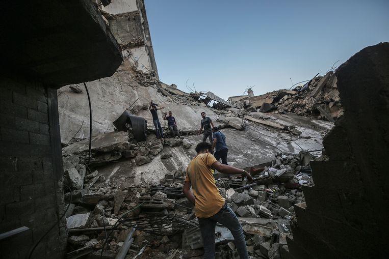 Palestijnen lopen tussen het puin van hun huizen, na een Israëlische luchtaanval op 19 mei. Beeld EPA