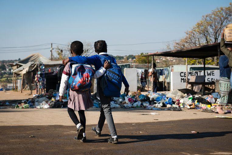 Twee schoolmeisjes steken een weg over in Zandspruit.  Beeld Bram Lammers