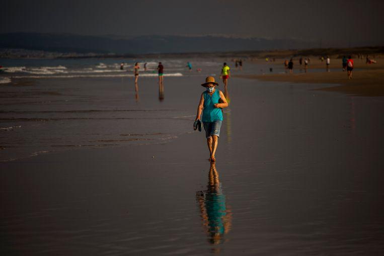 Een toerist op het strand van in Zahara de los Atunes, Zuid-Spanje. Beeld AP