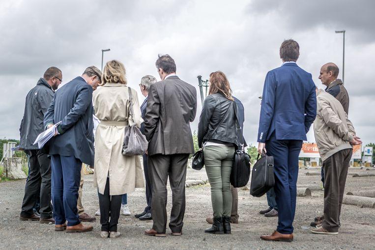 Een deurwaarder bezoekt samen met gemeenteraadsleden en vertegenwoordigers van bouwheer Ghelamco parking C in Grimbergen om vast te stellen waar de buurtweg loopt. Beeld Jan Aelberts