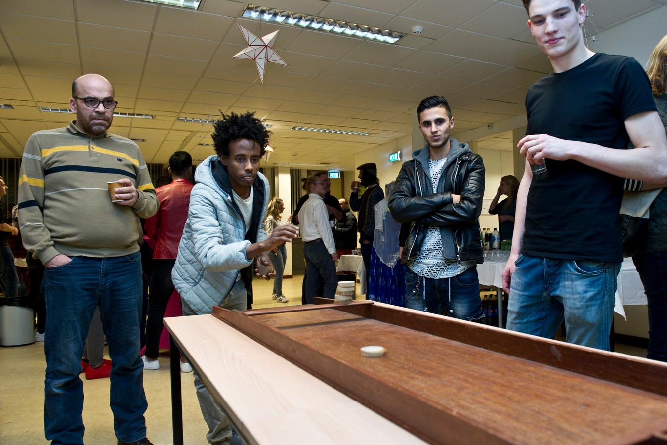 Bewoners en asielzoekers treffen elkaar in de gemeenschappelijke ruimte van het azc aan de Stieltjesstraat in Nijmegen.