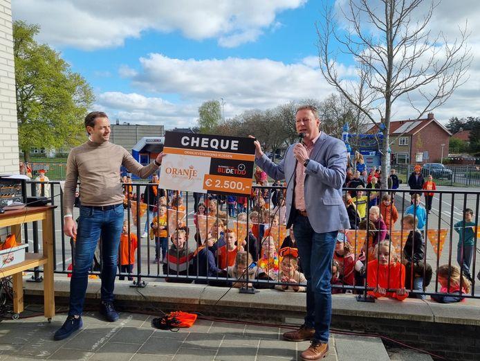 Olav Roeterdink van de Oranjevereniging Rijssen ontvangt een cheque van voorzitter Jan Willem ter Harmsel van Businussclub Bij de Tijd. Daarvan werden Koningsdagtasjes gekocht waarvan de eerste vrijdag zijn uitgedeeld aan de kinderen van de Klimopschool.