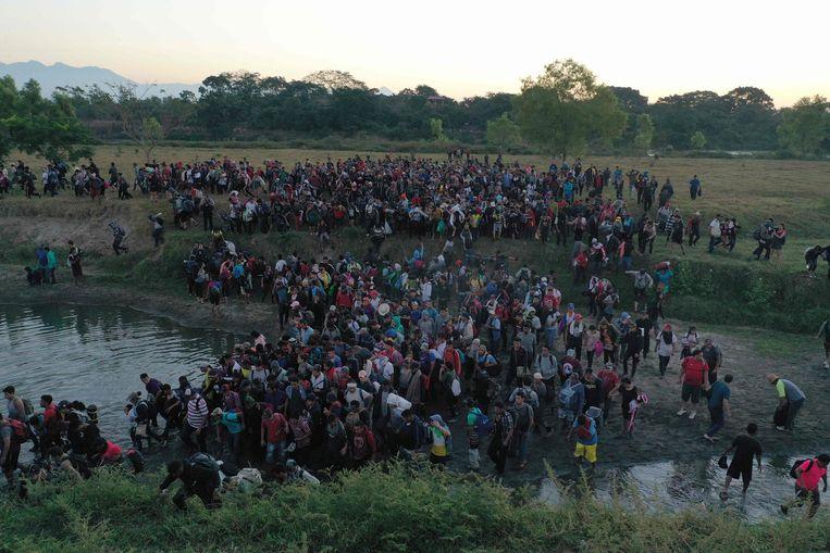 Migranten uit Centraal-Amerika op weg naar de VS steken massaal de rivier Suchiate over van Tecun Uman, Guatemala, naar Ciudad Hidalgo, Mexico. Beeld AFP