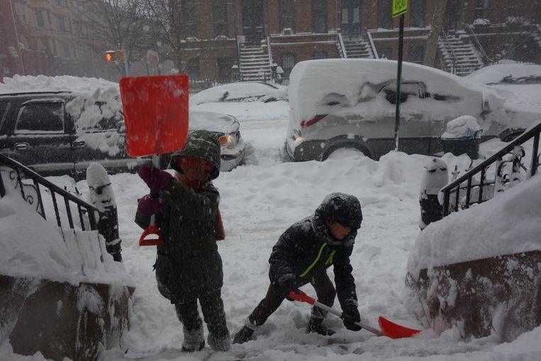 Kinderen in Brooklyn maken een trap sneeuwvrij. Beeld Michael Persson