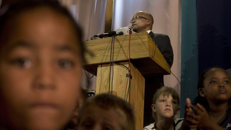Kinderen tijdens een wonen een herdenkingsdienst bij in een kerk in Johannesburg. President Jacob Zuma staat in het spreekgestoelte. Beeld ap