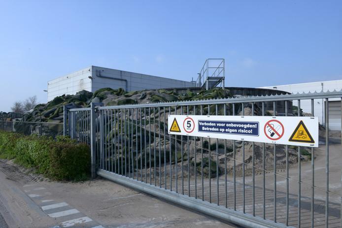 Kunstgrasrollen liggen hoog opgestapeld  op het terrein bij Tuf Recycling in Dongen.