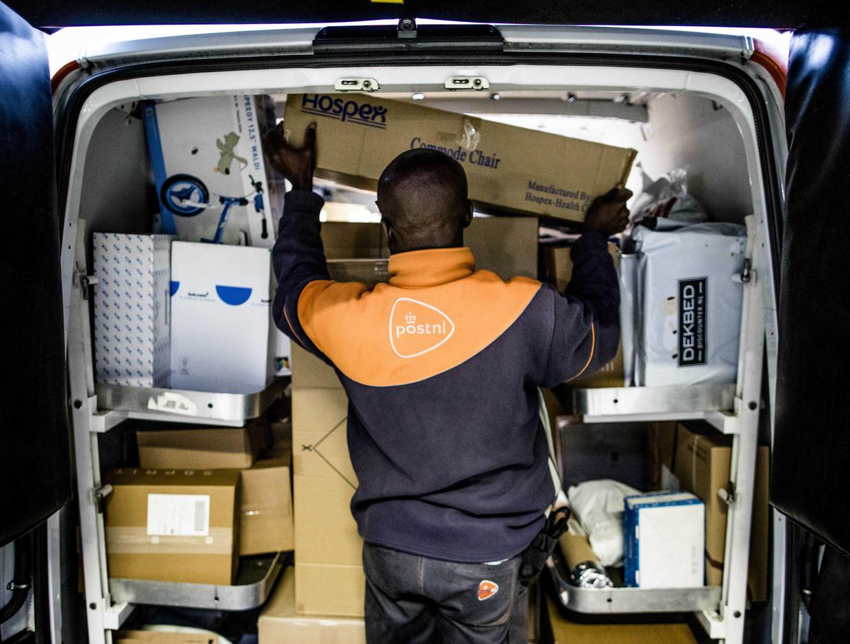 Een koerier van het Nederlandse PostNL aan het werk. E-commerce heeft geen grenzen. Beeld ANP
