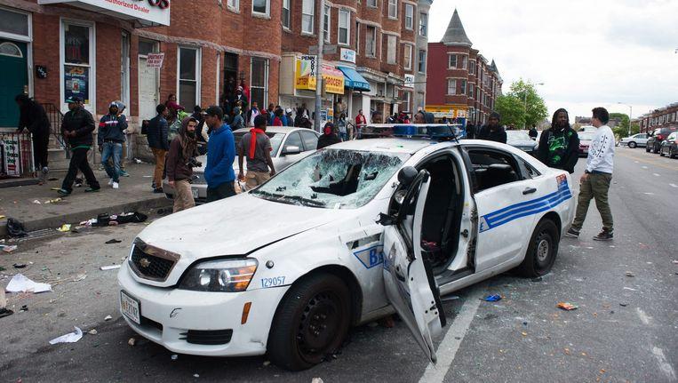 Een vernielde politiewagen nabij het winkelcentrum in Mondawmin, Baltimore. Beeld EPA