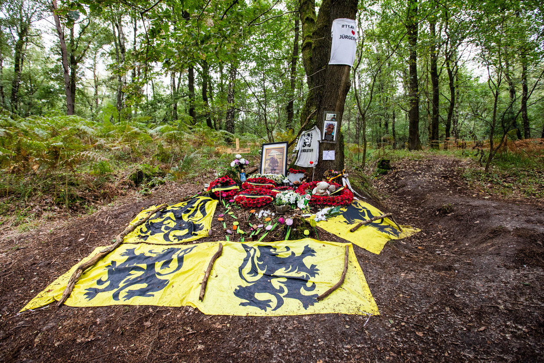 Op de plek waar Conings' lichaam in juni gevonden werd, hebben fans leeuwenvlaggen en bloemenkransen neergelegd. Beeld Mine Dalemans