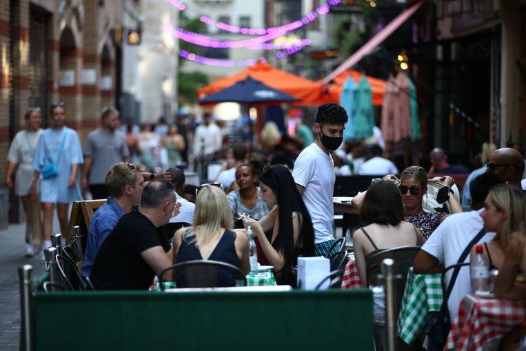 Mensen dineren op een terras in Londen. Mondmaskers dragen en afstand houden is niet langer een wettelijke verplichting. Beeld Getty Images