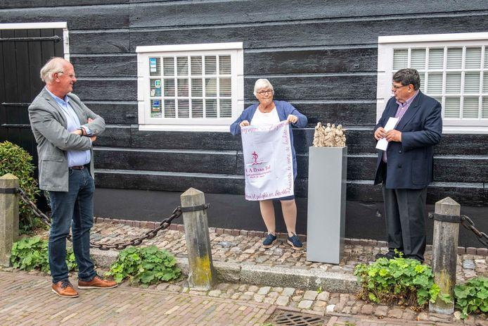 Omdat hij meer dan dertig jaar huisarts van Veere was, krijgt René van Tol (links) een cadeau van Lieneke Kamphuis en Jan Paul Loeff van de Stadsraad. Een beeldje met mensen 'die reikhalzend uitkijken naar een goede heelmeester'.