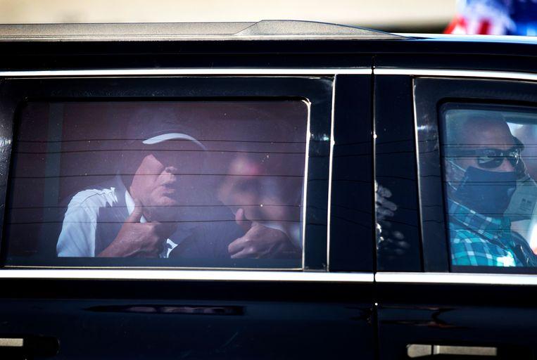 Oud-president Trump laat zich vanuit zijn auto toejuichen door aanhangers die langs de straat staan in West Palm Beach, Florida.  Beeld Joe Raedle / Getty Images
