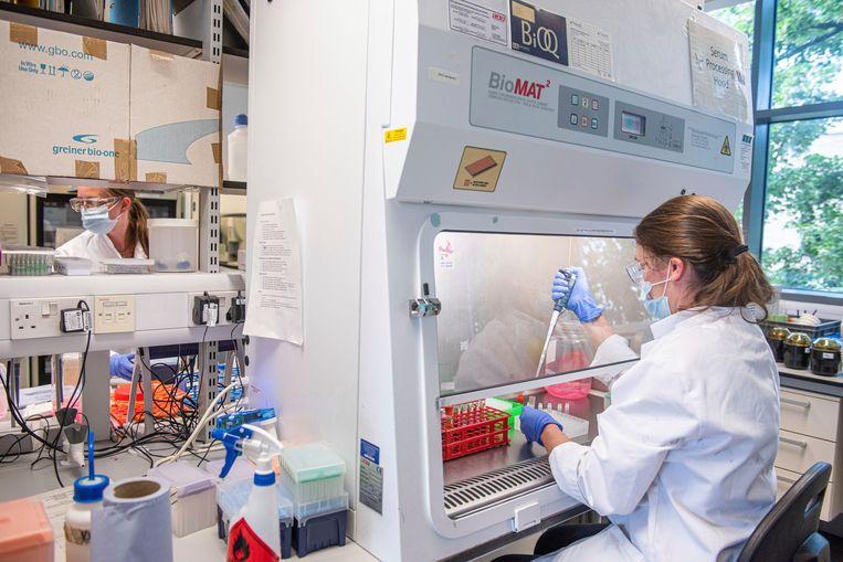 Een medewerker van het farmaceutische bedrijf AstraZeneca bij de Universiteit van Oxford, werkt in beschermende kleding aan een vaccin tegen covid-19.  Beeld AP