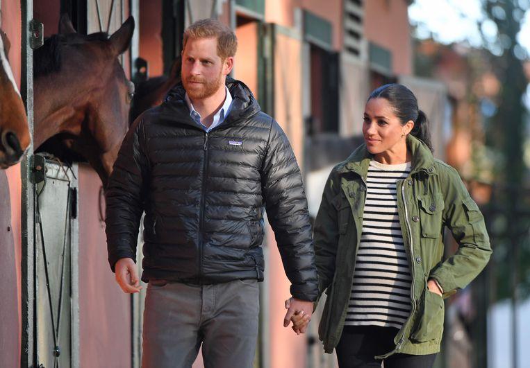 De Britse prins Harry en zijn echtgenote Meghan verliezen hun koninklijke titels. Beeld AFP