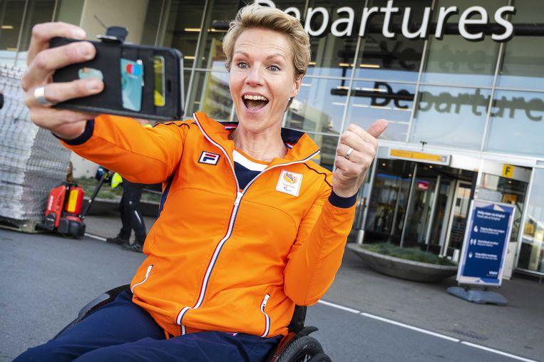 Chef de mission Esther Vergeer neemt voor vertrek naar Tokio nog een selfie op Schiphol. Beeld ANP