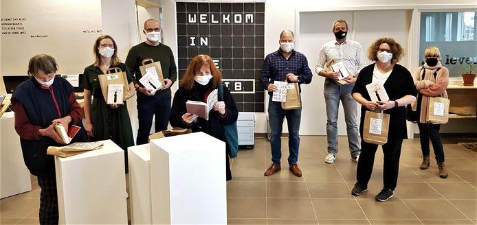 Leden van de bibliotheekraad, bibliothecaris Christophe Nassen (vierde van rechts) en cultuurschepen Pieter-Jan Parrein (derde van rechts) tonen het boekenpakket.