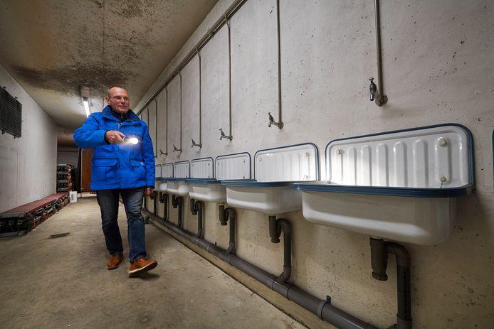 Arno van Orsouw toont  de eindeloze rij wasbakken in de atoomschuilkelder.