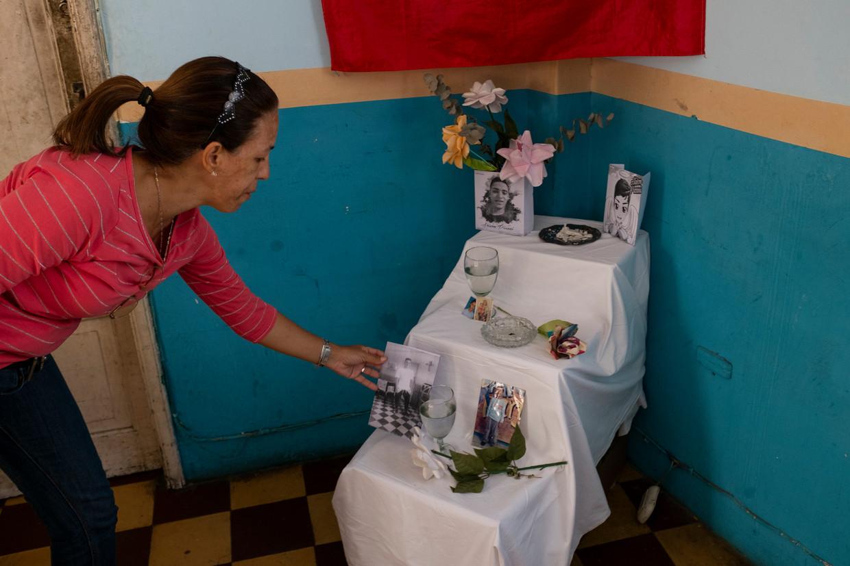 Nivea Troloroco zet een foto op het altaar voor haar neef Alixon Pisani, die op 22 januari werd doodgeschoten bij de protesten in Catia, een van de sloppenwijken in Caracas.  Beeld Marco Antonio Bello
